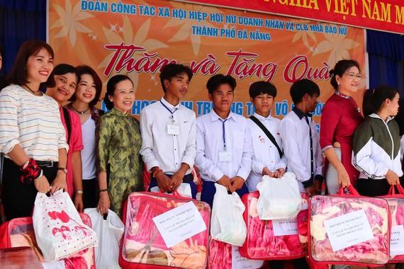 Đại diện Hiệp hội nữ doanh nhân và CLB nhà báo nữ thành phố Đà Nẵng trao quà cho học sinh người Cơ Tu