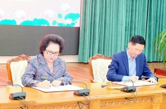 Tran Vinh Tuyen (R), deputy chairman of the HCM City People's Committee, and Ly Kim Chi, chairwoman of the HCM City Food and Foodstuff Association, at the signing ceremony in HCM City. (Photo: VNA)