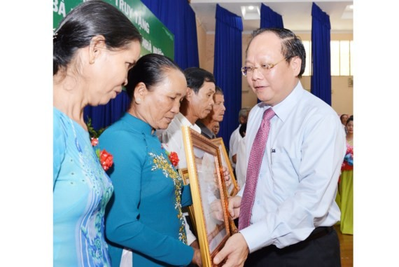 Standing Deputy Secretary of Party Committee of Ho Chi Minh City, Tat Thanh Cang awards the Heroic Vietnamese Mothers title to a mother's relatives. (Photo: Sggp)