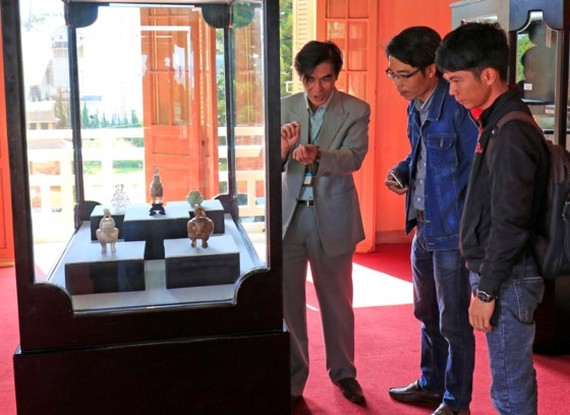 Visitors contemplate artifacts at the exhibition