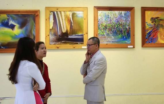 Painter Vo Trinh Bien ( R) at the exhibition (Photo: Sggp)