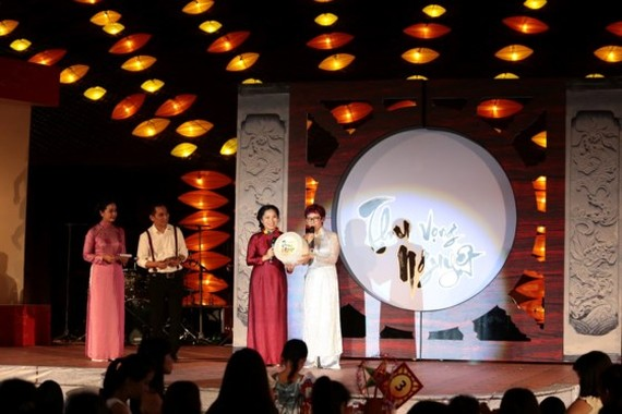 Ms. Tran Mai Anh (in white Ao Dai), represents the Thien Nhan and Friends Fund to receive the donation from the organization board of the Mid-Autumn charity festival. (Photo: Sggp)