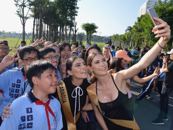 Beauties take selfie with young people in HCM City . (Photo: Sggp)