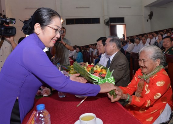 HCMC deputy Party Secretary Vo Thi Dung offers flowers to a Vietnamese heroic mother at the ceremony. (Photo: Sggp)
