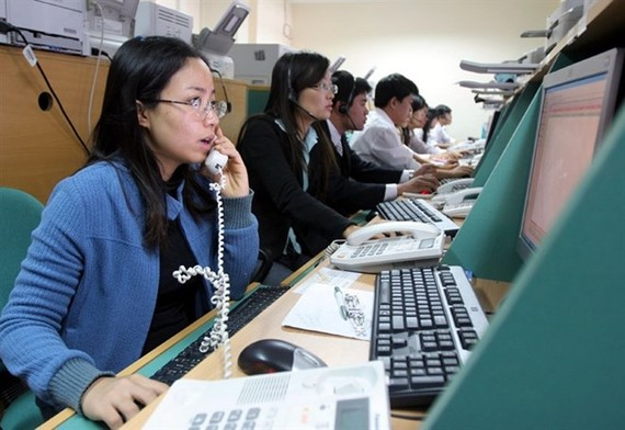 Stock brokers work on the Hanoi Stock Trading Centre (Photo: VNA)