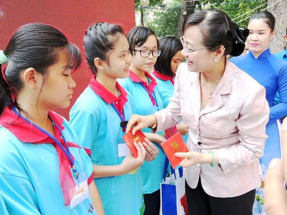 Chairwoman of the city People's Council Nguyen Thi Quyet Tam present gifts to disadvantaged children. (Photo: Sggp)