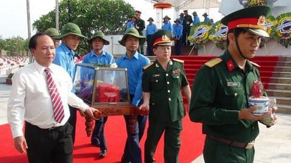 Local staff and army personnel carry the coffin containing a set of remain. (Photo:Sggp)