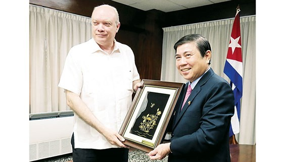 Chairman of the People's Committee of HCMC Nguyen Thanh Phong presents a gift to the Cuban Minister of Foreign Trade and Investment, Rodrigo Malmierca Diaz. (Photo: Sggp)