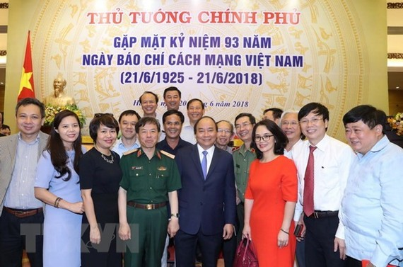 Prime Minister Nguyen Xuan Phuc (front, fourth, right) and representatives of press agencies pose for a photo at the meeting in Hanoi on June 20 (Photo: VNA)