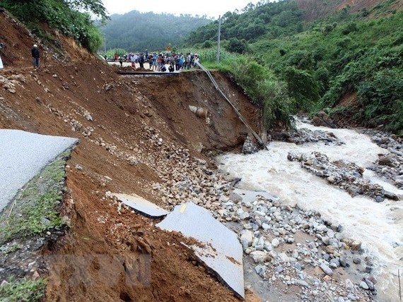 A section of National Road 32 is destroyed by flood (Photo: VNA)