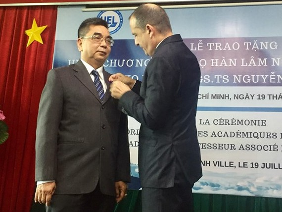 Consul General of France in HCM City Vincent Floreani presents Order of Academic Palms of France to Assoc. Prof. Dr. Nguyen Ngoc Dien. (Photo: Sggp)