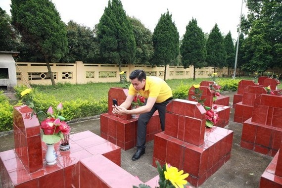 A Vietnam Post staff member takes pictures of a martyr's tomb while collecting data for the web portal (Photo: VNA)