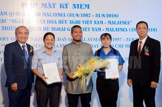 President of HCMC Union of Friendship Organization (HUFO), Huynh Minh Thien and Chairman of the Vietnam-Malaysia Friendship Association (VMFA) of HCMC Tran Ngoc Son congratulate the Vietnam-Malaysia Friendship Association of Phu Nhuan district