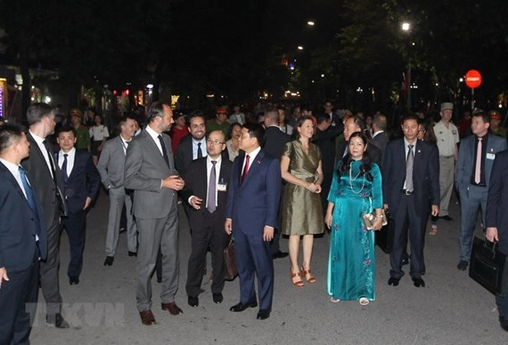French Prime Minister Edouard Philippe and Chairman of Hanoi People's Committee talk during their walk around Hoan Kiem Lake (Photo: VNA)