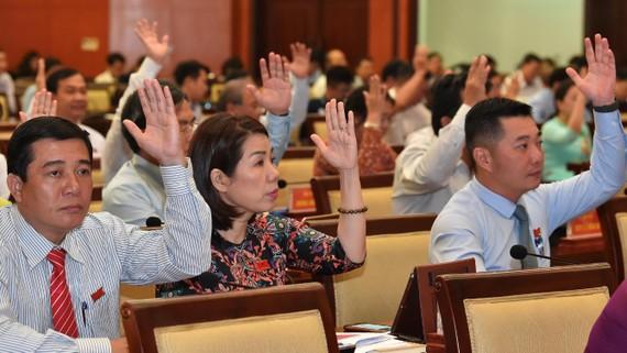 Các đại biểu HĐND TPHCM biểu quyết thông qua nghị quyết kỳ họp..Ảnh: VIỆT DŨNG