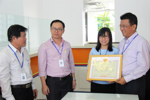 Director Ngo Tan Cu presents certificate of merit and cash gift to Ms. Anh (Photo: SGGP)