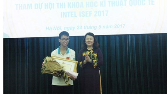 Deputy Education Minister Nguyen Thi Nghia presents certificate of merit to Pham Huy (Photo: SGGP)