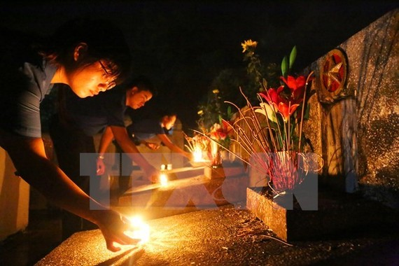 Candle lighting and incense offering to war martyrs. President Tran Dai Quang has signed decision to present gifts to Vietnamese heroic mothers, war martyrs' relatives and invalids. (Photo: VNA)