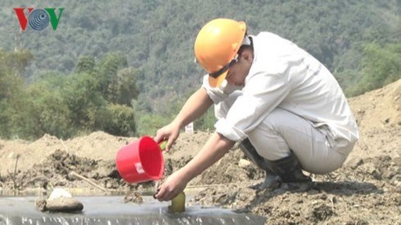 A worker collects water samples at the dam collapse site in the central province of Nghe An. (Photo: vov.vn)