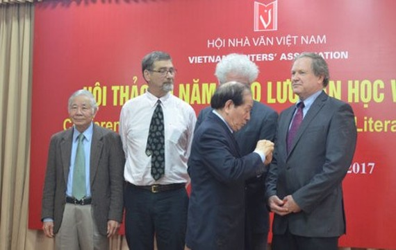 Huu Thinh, Chairman of the Vietnam Alliance of Arts and Literature Associations and the Vietnam Writers' Association, presented insignia for the Vietnamese art and literature cause. (Photo: vietnamnet)