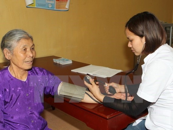 A doctor gives check-up to an elderly woman (Photo: VNA)