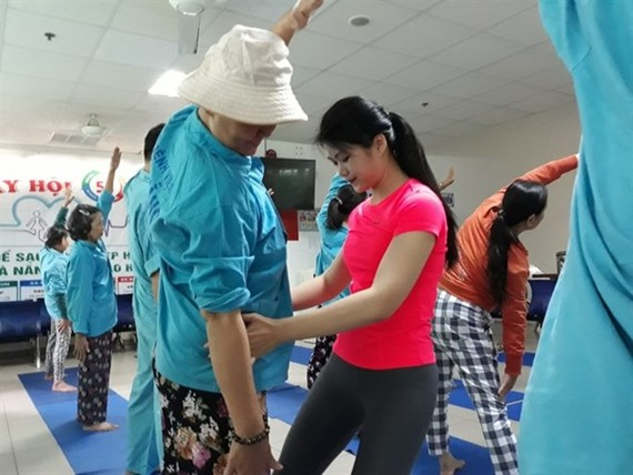 Dang Thi Quynh Nhu (center) adjusts body position for a cancer patient in her free yoga therapy class at the Da Nang City General Hospital. (Photo thanhnien.vn)