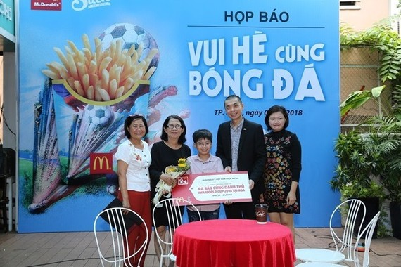 The organising board awards the ticket to Nguyễn Lê Thanh Sơn (middle) (Photo cand.com.vn)