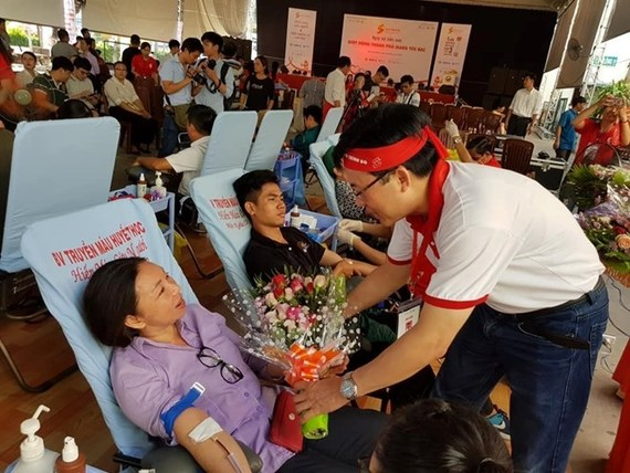 A member of the Red Journey's organising board presents flowers to a blood donor at the blood donation event in HCM City on June 22 (Photo: VNA)