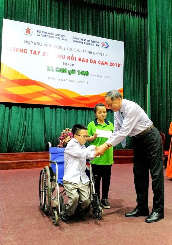 President of VAVA Sen. Lieut. Gen Nguyen Van Rinh gives gift to teacher Chu Quang Duc (Photo: SGGP)