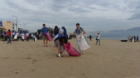 Participants at the 6th Global Environment Facility Assembly join hands to clean the beach in Da Nang city (Source: VNA)