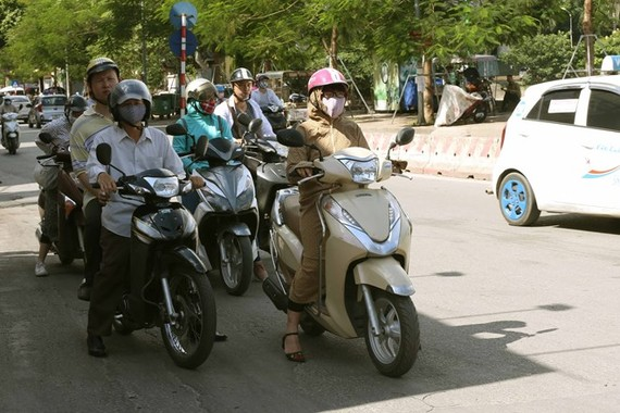Road users wait for the green light in the shadow to avoid the baking sun at the Truong Chinh - Ton That Tung intersection in Hanoi (Photo: VNA)