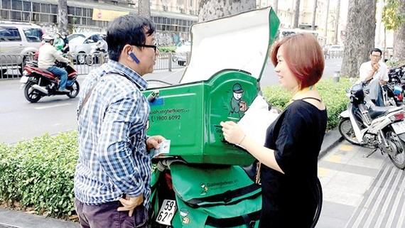 A man delivers goods to an online shopper (Photo: SGGP)