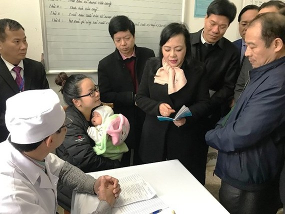Health Minister Nguyen Thi Kim Tien at a medical clinic talks about vaccination benefit to parents ( Photo SGGP)