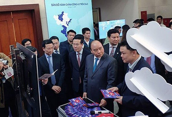 Prime Minister Nguyen Xuan Phuc, Head of the Central Propaganda Department of the Communist Party of Vietnam Vo Van Thuong, and Minister of Information and Communications Nguyen Manh Hung visited an exhibition booth on ICT achievements in the meeting