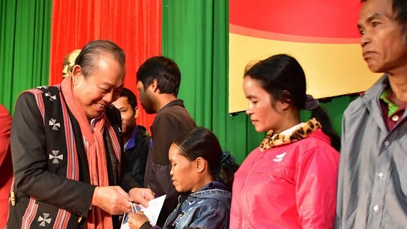 Deputy Prime Minister Truogn Hoa Binh gives gifts to poor people in A Luoi District (Photo: SGGP)