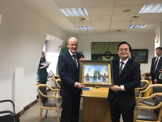 Vietnamese Minister of Education and Training Phung Xuan Nha (R) presents a gift to Minister of State at the UK Department for Education Nick Gibb (Photo: VNA)