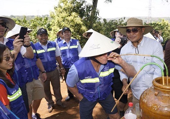 Vietnam's Tourism Ambassador Greg Norman tries ruou can (wine drunk from a jar through pipes) in the Central Highlands province of Dak Lak (Photo: vnexpress.net)