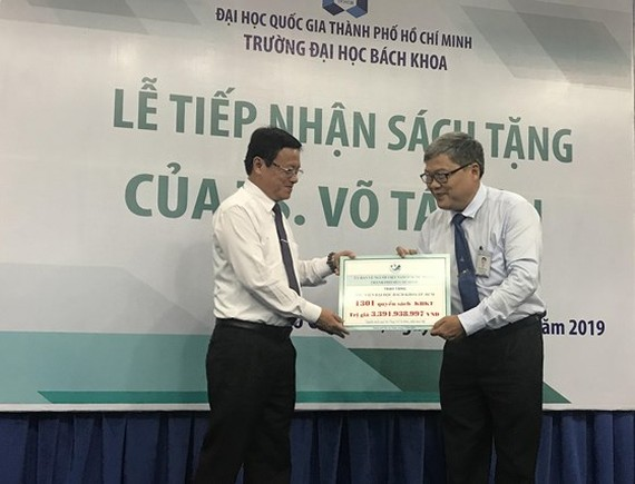 Deputy chairman of Committee for Overseas Vietnamese Vo Thanh Chat (L) gives the books to HCMCUT representative (Photo: SGGP)