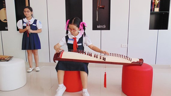 Students in Lac Long Quan Primary School (located in District 11) are performing a song with one traditional musical instrument