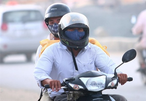 Motorbike riders in Hà Nội have to wear masks on a dusty highway section through Cau Dien - Nhon (Photo: VNA)