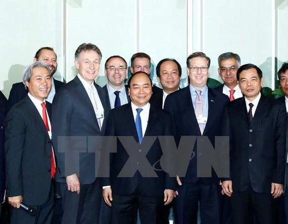 Prime Minister Nguyen Xuan Phuc (C) takes photo with entrepreneurs (Photo: VNA)