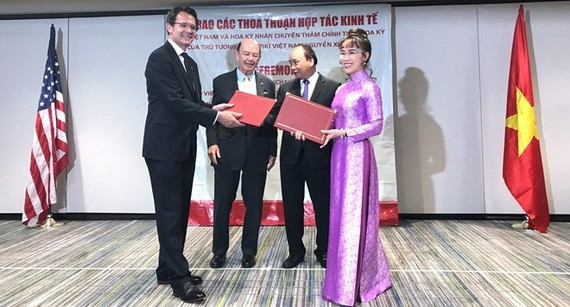 Vietjet's President and CEO Nguyen Thi Phuong Thao (front, right) and President and CEO of CFM International Gaël Méheust (front, left). Prime Minister Nguyen Xuan Phuc and US Secretary of Commerce Wilbur L. Ross, Jr (behind) are present at the signing ce
