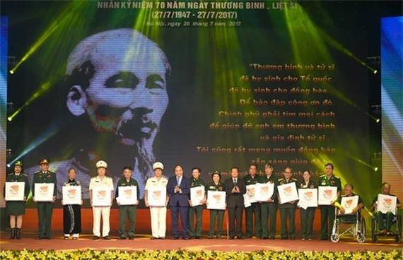 Prime Minister Nguyen Xuan Phuc presents gifts for revolutionary contributors at the event (Source: VGP)