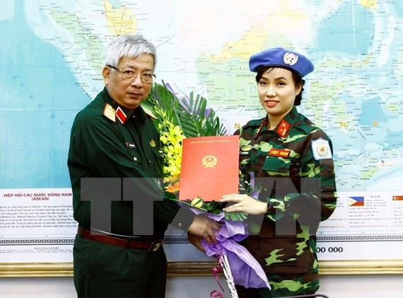 Deputy Minister of National Defence Senior Lieutenant General Nguyen Chi Vinh (L) hands over to Major Do Thi Hang Nga a decision sending her to UN peacekeeping mission in South Sudan (Photo: VNA)