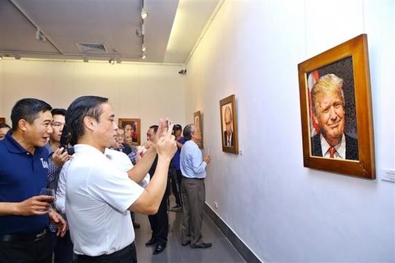 Visitors take a photo of a mosaic ceramic painting of US President Donald Trump (Photo: VNA)