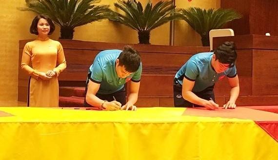 Vietnamese U23 footballers respectively sign names on national flag