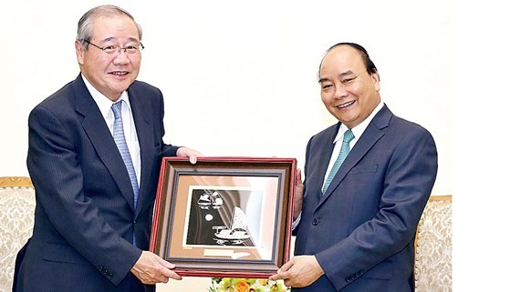PM Nguyen Xuan Phuc (R) offers a painting to Koichi Miyata, Chairman of Sumitomo Mitsui Financial Group (SMFG) cum Chairman of Sumitomo Mitsui Banking Corporation (SMBC) of Japan (photo:VNA)