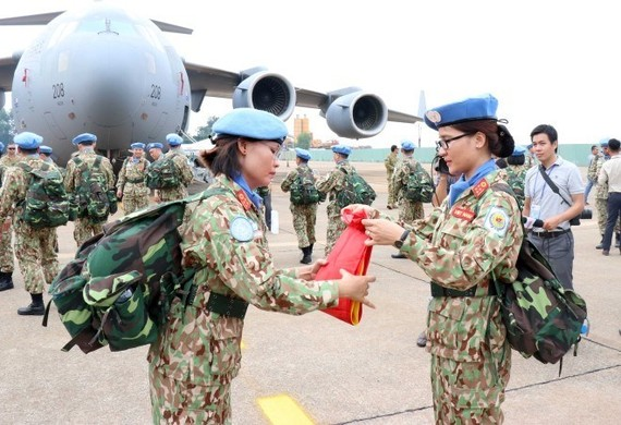 Two members of the level-2 field hospital folded the military flag before the departure of the peacekeeping force in October 2018. (Photo: VNA)