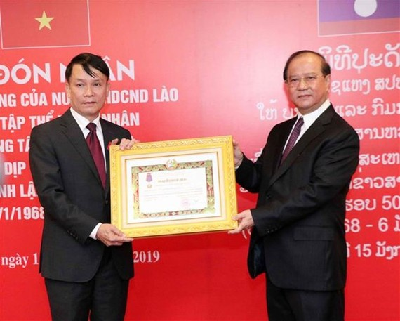 VNA General Director Nguyen Duc Loi (L) receives the second-class Isala (Freedom) Order bestowed by the Lao State. (Photo: VNA)
