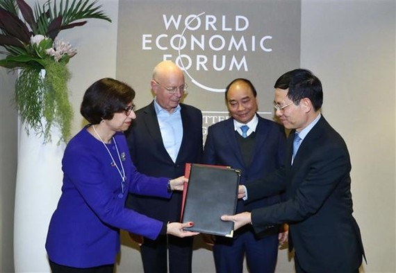 PM Nguyen Xuan Phuc (blue tie) and WEF Founder and Executive Chairman Klaus Schwab witness the signing of  an agreement between the WEF and Vietnam on building a centre for the Fourth Industrial Revolution. (Photo: VNA)